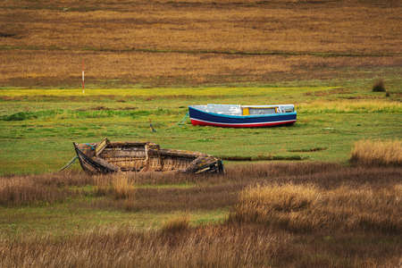 The wrecks of two boats in the grass, seen in Askam-in-Furness, Cumbria, England, UK 写真素材