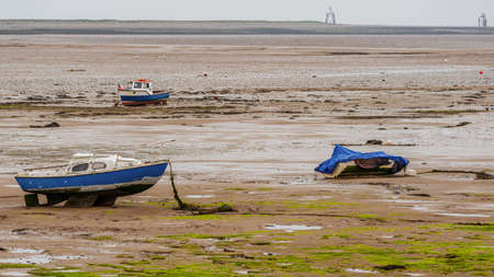 Three boats in the mud of the Walney Channel, seen from the road to Roa Island, Cumbria, England, UK