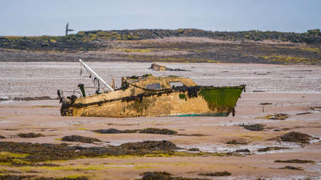 A damaged boat in the mud of the Walney Channel, seen from the road to Roa Island, Cumbria, England, UK 写真素材
