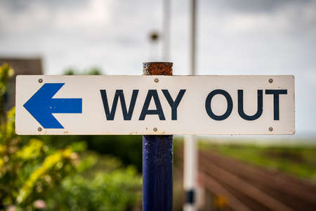 Sign: Way Out, with blurry background, seen in Kirkby-in-Furness, Cumbria, England, UK