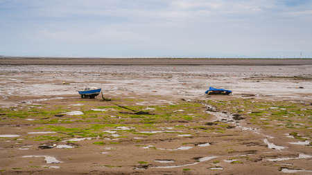 Two boats in the mud of the Walney Channel, seen from the road to Roa Island, Cumbria, England, UK