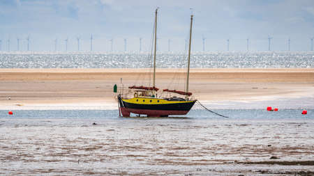 A boat in the low tide with the Ormonde Wind Farm in the background, seen in Haverigg, Cumbria, England, UK