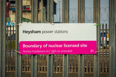 Heysham, Lancashire, England, UK - April 30, 2019: Sign at the fence of Heysham Nuclear Power Station - Heysham power stations, Boundary of nuclear licensed site Редакционное