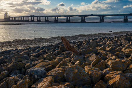 A piece of driftwood, with The Prince of Wales Bridge in the background, seen from Severn Beach, South Gloucestershire, England, UK