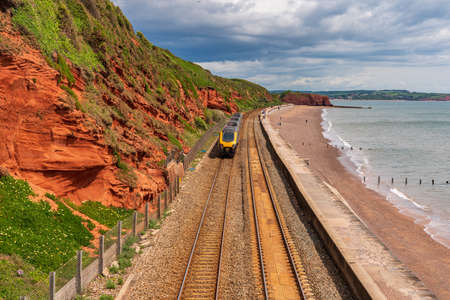 Dawlish, Devon, England, UK - June 05, 2019: The Red Rock Beach with a train passing