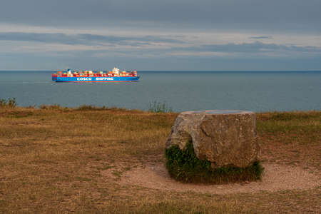 Berry Head, Torbay, England, UK - June 06, 2019: A large stone at the coast of the British Channel with a container ship passing by Редакционное