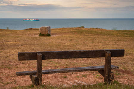 Berry Head, Torbay, England, UK - June 06, 2019: A bench overlooking the English Channel with a container ship passing by