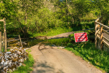 Sign: Temporary Road Surface, with a road leading over the Scandal Beck near Smardale, Cumbria, England, UK