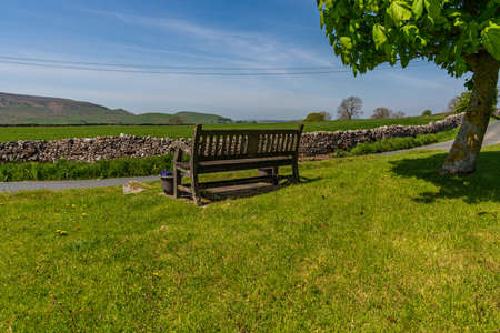A bench with a view over the Yorkshire Dales near Hartlington, North Yorkshire, England, UK Фото со стока