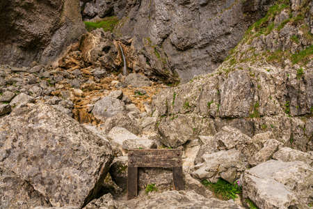 Sign: Take care difficult climb up, with a waterfall in the background, seen at the Gordale Scar near Malham, North Yorkshire, England, UK Stockfoto