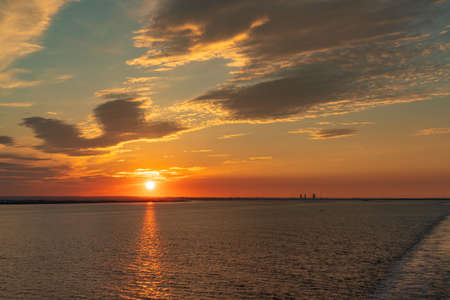 The setting sun and evening clouds over the River Humber near Paull, East Riding of Yorkshire, England, UK