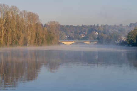 Muelheim an der Ruhr, North Rhine-Westfalia, Germany - October 31, 2019: Early morning mist at the shore of the River Ruhr