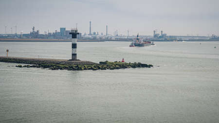 Hook of Holland, Rotterdam, South Holland, Netherlands - April 23, 2019: A harbour light and a ship entering Europoort