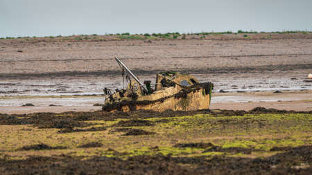 A damaged boat in the mud of the Walney Channel, seen from the road to Roa Island, Cumbria, England, UK