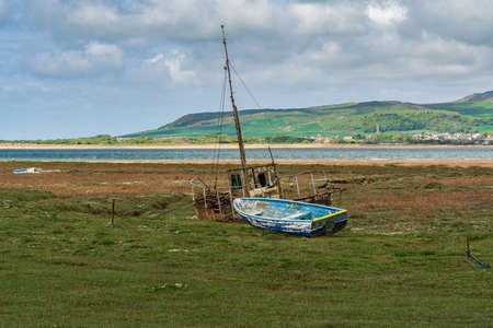 The wrecks of two boats in the grass, seen in Askam-in-Furness, Cumbria, England, UK