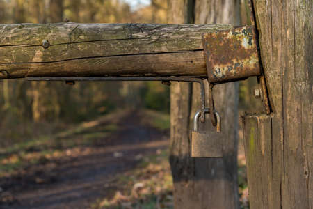 Padlock on a wooden gate with a footpath into the forest in the background, seen at Saarner Mark, Muelheim an der Ruhr, North Rhine-Westphalia, Germany Imagens