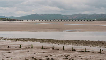 Canal Foot, Cumbria, England, UK - May 1, 2019: Low tide at Morecambe Bay with a train passing on the Leven Viaduct in the background
