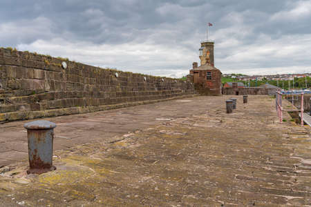 Whitehaven, Cumbria, England, UK - May 03, 2019: Grey clouds over the buildings on the Old Quay Editorial