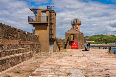 Whitehaven, Cumbria, England, UK - May 03, 2019: Wall and buildings on the Old Quay