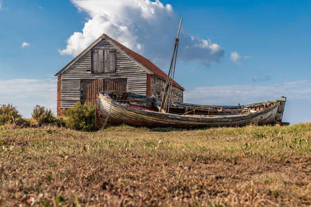 Thornham, Norfolk, England, UK - April 24, 2019: An old stone barn in Thornham Old Harbour with a wooden sailing boat in front of it
