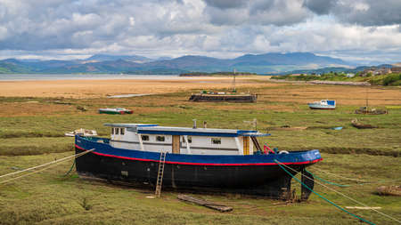 Askam-in-Furness, Cumbria, England, UK - May 2, 2019: Boats in the grass, with clouds over the Lake District National Park in the background