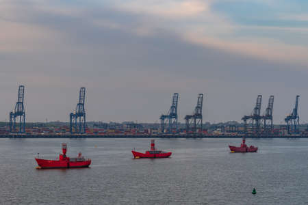 Felixstowe, Suffolk, England, UK - April 23, 2019: Lighthouse boats and Port Cranes in Felixstowe Harbour Editorial