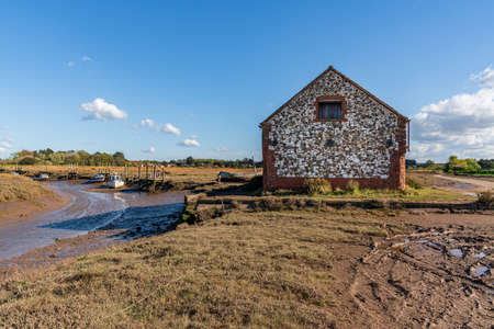 Thornham, Norfolk, England, UK - April 24, 2019: An old stone barn in Thornham Old Harbour with some boats in the River Hun at low tide Editorial