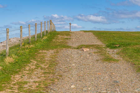 Workington, Cumbria, England, UK - May 04, 2019: Walking up to a hill with a cross on it