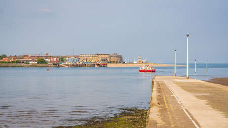 Knott End-on-Sea, Lancashire, England, UK - April 30, 2019: The ferry pier with a ferry leaving, and the River Wyre and Fleetwood in the background