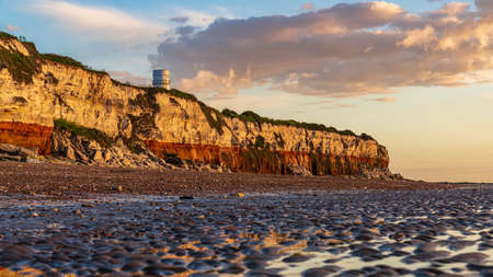 Hunstanton, Norfolk, England, UK - April 25, 2019: Evening light and clouds over the Lighthouse and the Cliffs