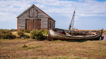 Thornham, Norfolk, England, UK - April 24, 2019: An old stone barn in Thornham Old Harbour with a wooden sailing boat next to it