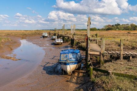 Thornham, Norfolk, England, UK - April 24, 2019: Boats in the low tide at Thornham Old Harbour