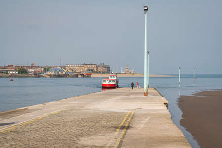 Knott End-on-Sea, Lancashire, England, UK - April 30, 2019: The ferry pier with a ferry approaching, and the River Wyre and Fleetwood in the background