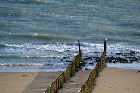Groynes into the sea on the Dutch coast Standard-Bild - 115570293