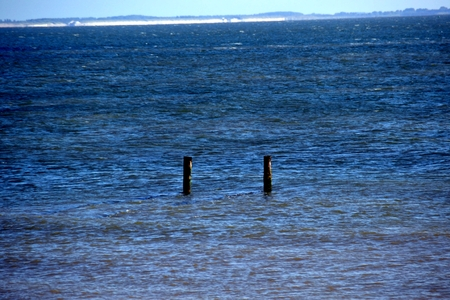 Two groynes stick out of the water at high tide Standard-Bild - 119653317