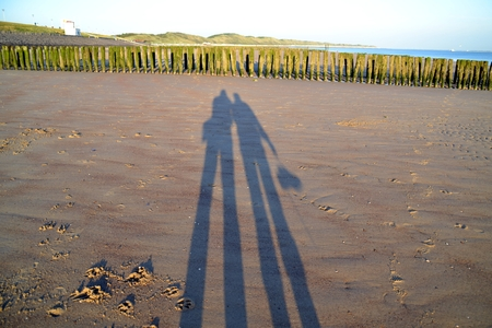 Two long shadows on a Dutch beach Banco de Imagens