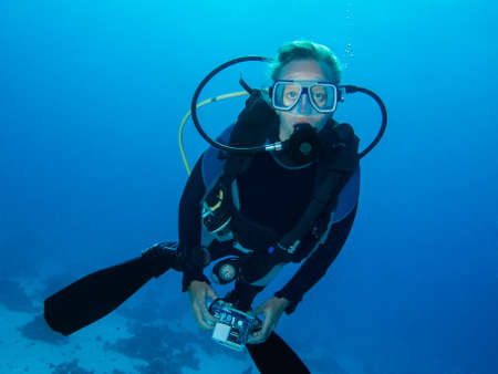 divers: Female scuba diver and underwater photographer Stock Photo