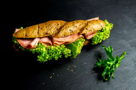 complete healthy deli sandwich kornspitz whole grain filled with meat slices and salad over dark background with copy space Stock Photo