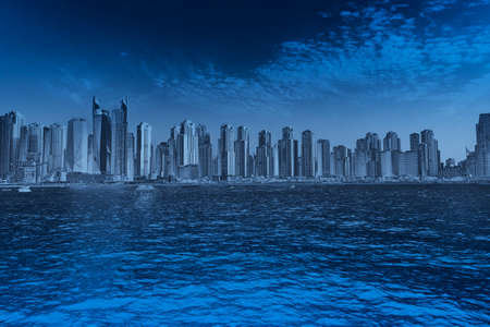 big skyscrapers town landscape, font view cityscape panorama from the sea with waves illustration blue monochromatic