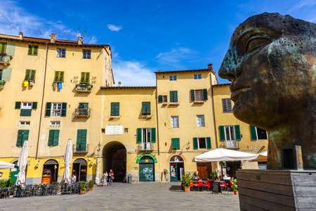 Lucca, Tuscany Italy - 09.15.2017: amphitheatre square with the Igor Mitoraj old big head sculpture