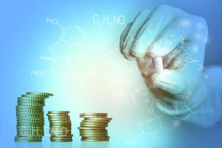 medicine industry concept blue background hand holding drug with coin stacks and medicine formulas Stok Fotoğraf