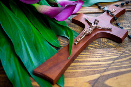 Cross with jesus christ on a wooden background with a purple calla and chaplet - religious easter lent concept
