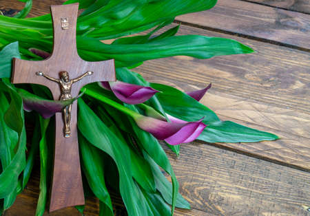 Cross with jesus christ on a wooden background with a purple calla - religious easter lent concept background