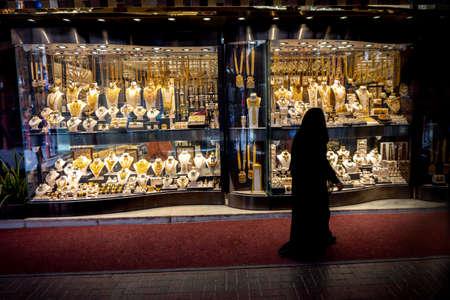 muslim woman in balck burqa view the windows in the gold souk in Dubai Stock Photo