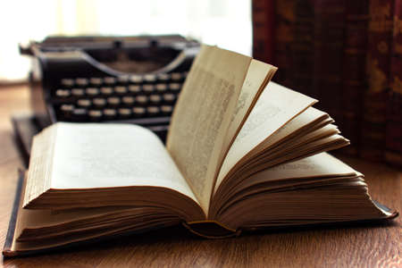 Old vintage book with natural window backlight and and old typewriter in the background bibliography literature concept