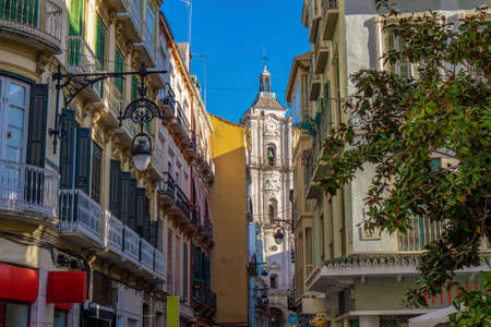 tower of inglesia san juan bautista church at the end of an narroe old town street in Malaga spain spanish architecture