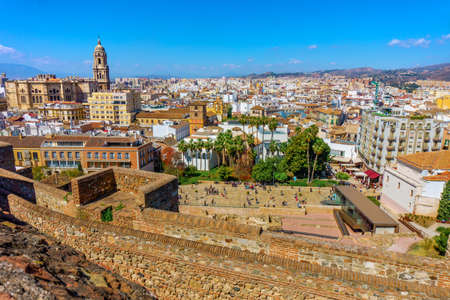 Panorama cityscape aerial view of Malaga, Spain. Santa Iglesia Cathedral Basilica of Lady of Incarnation from the Alcazaba castle and tourists on the street