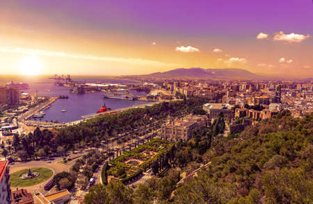 Aerial panoramic view of Malaga city, Andalusia, Spain and the sea in late purple sunset