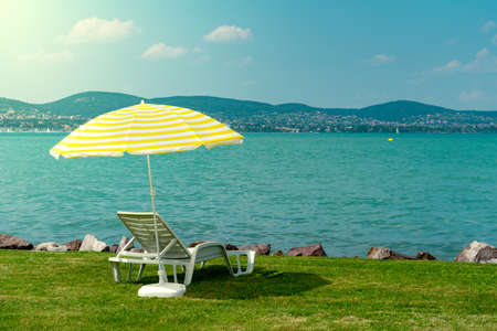 Stylish lounger plastic sunbed with yellow stripes sunshade beach umbrella on the green grass on beach at summer under open sky. Sunbed intended for cold shadow on convenient lounger at Lake Balaton Stockfoto - 126748122