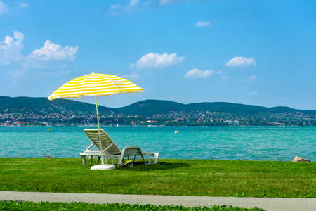 Stylish lounger plastic sunbed with yellow stripes sunshade beach umbrella on the green grass on beach at summer under open sky. Sunbed intended for cold shadow on convenient lounger at Lake Balaton